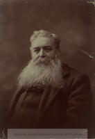Cusack in older age, bust only, dressed in heavy woollen coat and shirt of same  material, looking at the camera.