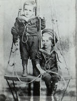 Black-and-white photograph and later copy, with portrait of Michael [Dominic] and John [Aloysius Cusack], sons of Michael and Margaret Cusack, as young children, both wearing sailors' suits and posing on a structure resembling a mast, a crow's nest, and s