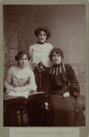 Black-and-white studio photograph of three young women, two seated and one standing behind them, all in their early 20s, two wearing white blouses and black skirts, one (on right) dressed in dark dress.