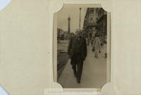 Black and white photograph of [John Cusack], walking up O'Connell Street from the direction of the River Liffey, with Nelson's Pillar in the background.