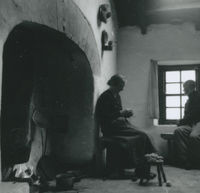 Photograph of Annie Hernon knitting close to a cottage hearth.