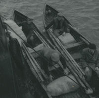 Photograph 2 currachs beside a large boat for the unloading of provisions.