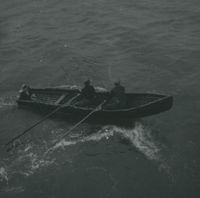 Photograph of 2 men rowing a currach.