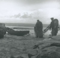Photograph of 2 men carrying fishing nets down to a currach.