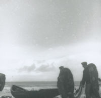Photograph of 2 men carrying fishing nets to a currach.