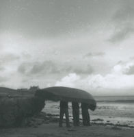Photograph of 3 men carrying a currach down to the sea.