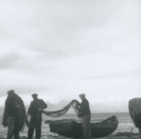 Photograph of 3 men sorting out fishing nets beside a currach.