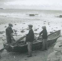 Photograph of 3 men loading fishing nets into a currach.