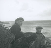 Photograph of 2 men standing beside a wall with fishing nets.