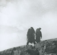 Photograph of 2 men carrying fishing nets over a crevice.