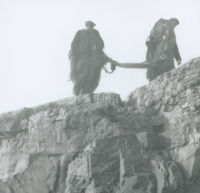 Photograph of 2 men carrying fishing nets along the top of some rocks, Aran Islands