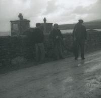 Photograph of 3 men sorting out fishing nets on a roadway.