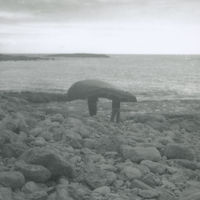 Photograph of 2 men carrying a currach down a rocky slope to the sea, Aran Islands