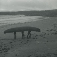 Photograph of 3 men carrying a currach up a beach away from the sea.