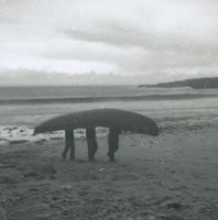 Photograph of 3 men carrying a currach up a beach from the sea.