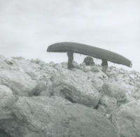 Photograph of 2 men carrying a currach through large boulders.