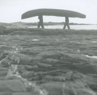 Photograph of 2 men carrying a currach across a rocky expanse beside the sea, Aran Islands