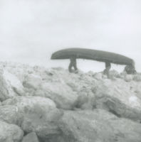 Photograph of 2 men carrying a currach through boulders, Aran Islands.