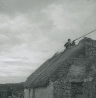 Photograph of 2 men on the top of a thatched cottage with a long rod.