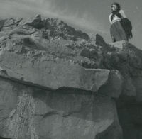 Photograph of Bridget Johnston standing up on a rocky cliff.