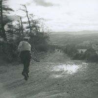 Photograph of Flor Crowley running down the road while road bowling.