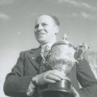 Photograph of Flor Crowley, road bowler, holding a silver cup.