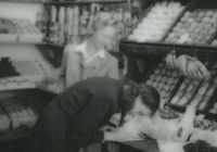 Photograph of Barbara Taft being assisted in the purchase of fruit in a shop.