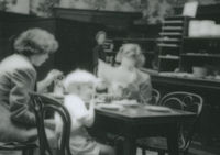 Photograph of Barbara Taft having tea with her son Sean and his nanny.