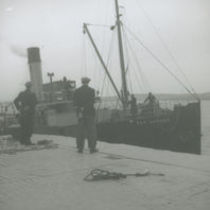 Photograph of two men watching the Dun Aengus steamer dock at Kilronan Pier, Aran Islands, so that it can be moored