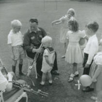 Photograph of children watching Leo Rowsome and a young piper play the uileann pipes in the grounds of the American Ambassador's residence, Phoenix Park, Dublin