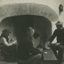 Photograph of two men playing cards, with a woman knitting.