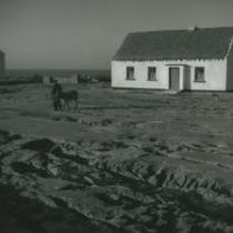 Photograph of a man walking away from his cottage, Aran Islands.