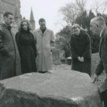 Photograph of Jean Ritchie and four others standing around a memorial stone.