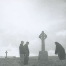 Photograph of two men and a woman in Kilmurvey graveyard.
