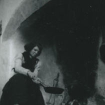 Photograph of Bridget Johnston cooking with a frying pan on an open fire.