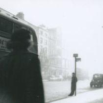 Photograph of a man waiting at a bus stop on a street in Dublin