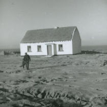 Photograph of a man and dog walking towards his cottage, Aran Islands.