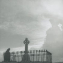 Photograph of a woman knelling at the O'Flaherty grave.
