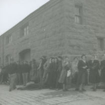 Photograph of passengers sheltering at Kilronan Pier, Aran Isalnds, waiting for the steamer to arrive