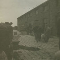 Photograph of men leading a pig along the Pier to load onto the Dun Aengus steamer, Aran Islands