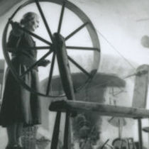 Photograph of Annie Hernon operating a spinning wheel.