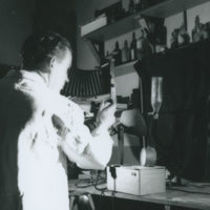 Photograph of a forensic scientist photographing a clock in a dark room at Garda Headquarters, Dublin Castle