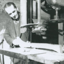 Photograph of a man cutting a piece of wood to make a hurley stick with a mechanical saw