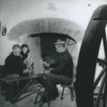 Photograph of two men playing cards, with a woman watching.