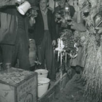 Photograph of a strawboy and wren boys partying with others at Lios Buí, Kilnamartry, Macroom, Co Cork