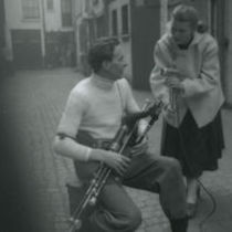 Photograph of Jean Ritchie recording Seamus Ennis playing the uileann pipes and singing.