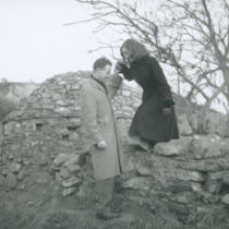 Photograph of a man helping a woman over a wall at Struell Wells.