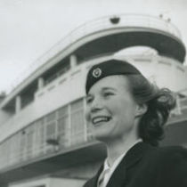 Photograph of the head and shoulders of a smiling air hostess standing outside at Dublin Airport